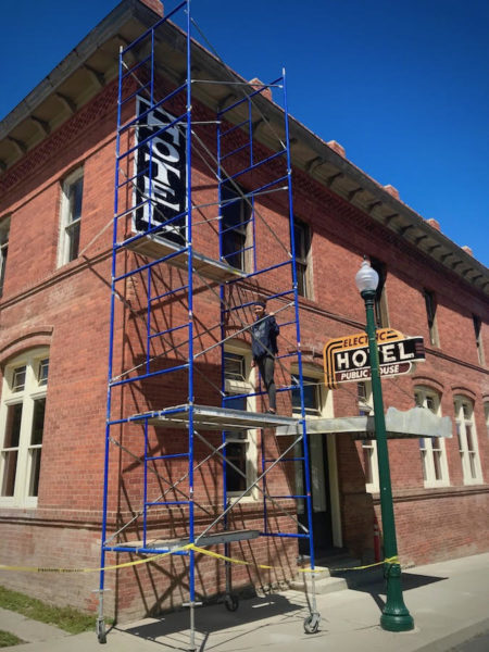 Kady Luzny inspects sign restoration
